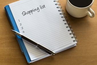 Shopping list written on notebook with cup of coffee